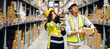Asian two engineer in helmet team order detail on tablet computer for checking goods and supplies on shelves with goods background in warehouse.logistic and business export
