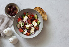 Greek Salad With Tomatoes, Cucumbers, Feta Cheese And Olives In A Bowl On Gray Stone Background
