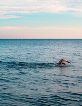 Vertical Shot Of A Man Swimming In A Beautiful Blue Ocean With Small Waves And A Bright Clear Sky