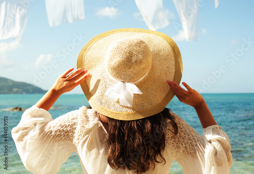 Tela Young woman in summer white dress with straw hat looking to a sky and sea