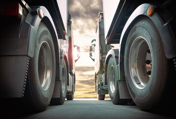 Two Semi Trucks Parked Side by Side at Sunset Sky. Road Freight by Truck Transportation.
