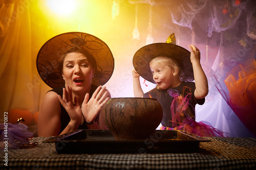 Obraz na plátně Beautiful brunette mother and cute little daughter looking as witches in special dresses and hats conjuring with a pot in room decorated for Halloween