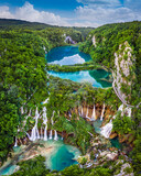 Plitvice, Croatia - Amazing view of the beautiful waterfalls of Plitvice Lakes in Plitvice National Park on a bright summer day with blue sky and clouds and green foliage and turquoise water