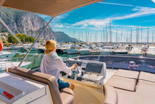 Sailing At The Sea. Beautiful Blond Woman Driving Yacht. Adult Woman Model In A White Shirt Sitting At The Wheel Of The Yacht And Begin To Drive Luxury Boat From The Port. Young Woman Driving Yacht