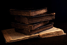 Stack Of Old Worn Shabby Jewish Books In Leather Binding On The Open Pages Of Machzor In The Dark. Closeup. Selective Focus. Low Key.