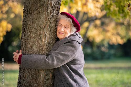 Fotografie, Obraz Senior woman hugging tree