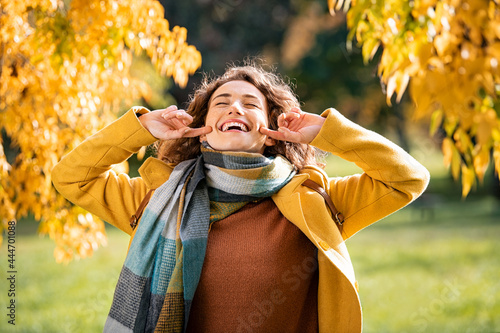 Fototapeta Joyful young woman laughing in autumn park