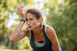 Tired mature runner wiping sweat after workout at park
