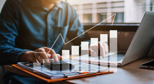 Businessman Or Financial Data Analysts Working With Laptop And Calculator Show Increase Market Share, Growth Of Profit Investment At Home Offiec.