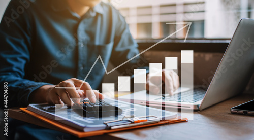 Fotografia Businessman or financial data analysts working with laptop and calculator show increase market share, growth of profit investment at home offiec