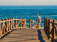 Hombre Con Sombrero Paseando Por Un Camino De Madera Frente Al Mar Junto A Su Perro