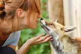 Happy woman kissing a fox in a farm