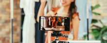 Young And Beautiful Asian Woman Blogger Showing Clothes In Front Of Smartphone Camera While Recording Vlog Video And Live Streaming At Her Shop
