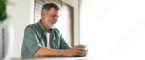 Obraz na plátně Happy mature man drinking coffee at home in the kitchen, enjoying hot drink in t