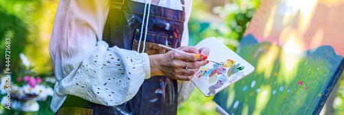 Fototapeta Beautiful young woman painting an art canvas outdoors in her garden