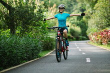 Woman No Handed Cycling On Tropical Park Trail In Summer