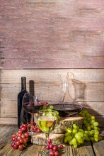 Glasses Of Red And White Wine With Sunshine And Shadows, With Bottle And Decanter, Bunch Of Grapes, On Wooden Background With Organic Pedestals, Autumn Harvest, Winery Concept