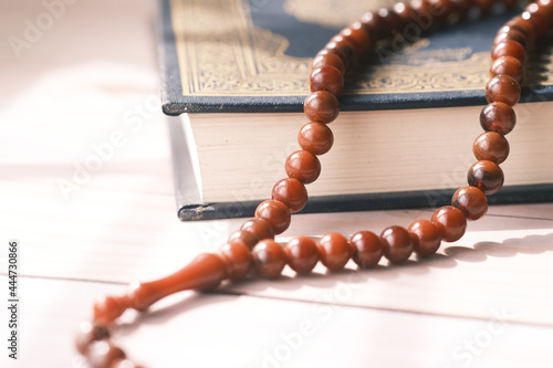 Fototapeta Holy book Quran and rosary on table, close up.