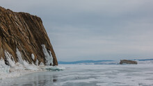 A Sheer Granite Rock, Devoid Of Vegetation, Rises On A Frozen Lake. Cracks On Layered Slopes. Icicles On The Base Of The Cliff. Reflection On Ice. A Small Island In The Distance. Cloudy. Baikal
