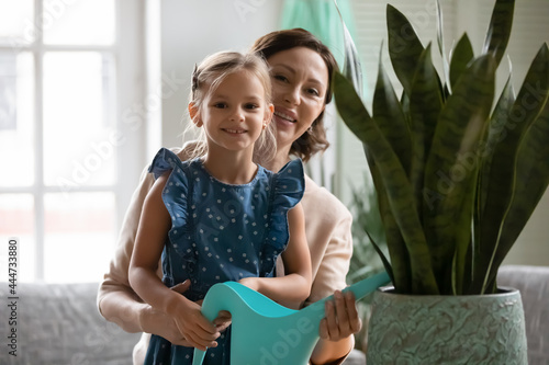 Obraz na plátne Portrait of loving happy old Caucasian 60s grandmother and small granddaughter water house plant together