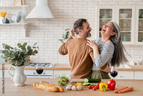 Fotografia Happy cheerful middle-aged mature couple family parents dancing together in the kitchen, preparing cooking food meal for romantic dinner, spending time together