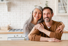 Cheerful Happy Mature Middle-aged Caucasian Couple Family Parents Husband And Wife Emracing Hugging, Spending Time Together In The Kitchen At Home, Sharing Love And Care. Social Distance Concept