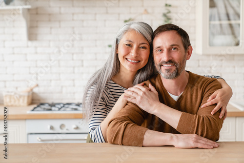 Fotomural Cheerful happy mature middle-aged caucasian couple family parents husband and wife emracing hugging, spending time together in the kitchen at home, sharing love and care