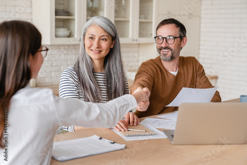 Foto Happy mature middle-aged family couple clients signs financial insurance, pensio