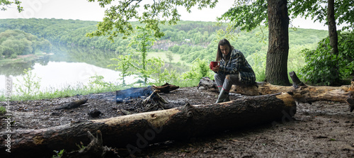 Canvas-taulu Girl with a cup of hot drink near the fire in nature.