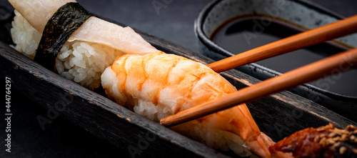 Obraz na płótnie Sushi sashimi set with shrimps and soy sauce served with wooden chopsticks and wasabi on black table