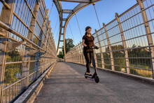 Caucasian Adult Woman Riding An Electric Scooter On A Path Across A Pedestrian Bridge Over The Highway In A Modern City. Taken In Fraser Heights, Surrey, Vancouver, British Columbia, Canada.