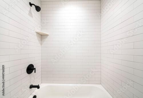 Alcove bathtub with black plumbing fixtures and white subway tiles wall surround Fototapeta