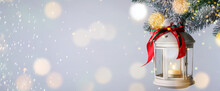 Christmas Lantern With Candle Hanging On Snowy Fir Tree Branch Against Light Background, Space For Text. Banner Design