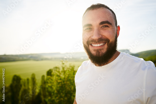 Fotografie, Obraz Young bearded man portrait outdoors in the mountains