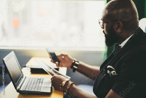 Side view of an elegant black man entrepreneur in a costume and glasses, working Fotobehang