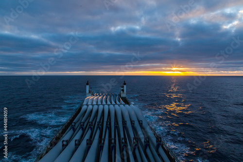 Fotografie, Obraz Transportation of blades for wind turbines on a cargo ship across the ocean at sunset