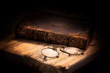 Imagen De Un Libro Antiguo Cerrado Y Con Adornos Metálicos En La Portada . Situado Sobre Una Tarima De Madera Y Con Unos Binoculares En Primer Plano Y Con Un Fondo Oscuro Y Cálido