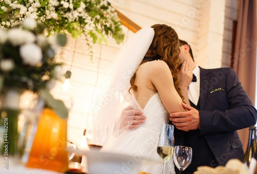 wedding couple kissing at table in decorated  restaurant close up Fototapet