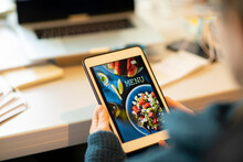 Woman Looking At Takeout Menu On Digital Tablet