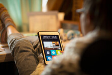 Woman Looking At Smart Home Automation On Digital Tablet Screen