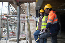 Male Construction Workers Talking At Construction Site