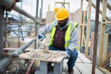 Male Construction Worker Mixing Concrete At Construction Site
