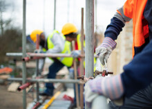 Construction Workers Assembling Scaffolding At Construction Site