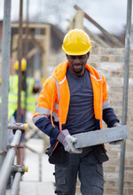Male Construction Worker Carrying Brick At Construction Site