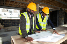 Male Architect And Foreman Looking At Blueprints At Construction Site