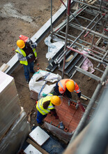Construction Workers With Bricks At Construction Site