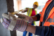 Close Up Construction Workers Using Tape Measure