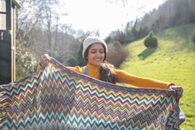 Young Woman Folding Blanket At Sunny Campsite