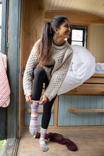 Young Woman Putting On Socks In Tiny Cabin Rental