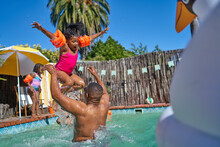 Father Throwing Daughter Into Air In Sunny Summer Swimming Pool